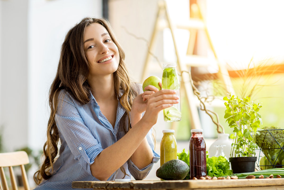 Beautiful happy woman sitting with drinks and healthy green food